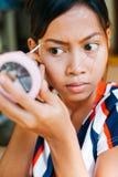 Young beautiful girl applying makeup. Girl coloring eyebrows with eyebrow liner Stock Photos