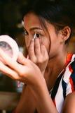 Young beautiful girl applying makeup. Girl coloring eyebrows with eyebrow liner Stock Images