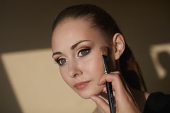 Young beautiful girl applying makeup by makeup Royalty Free Stock Photo