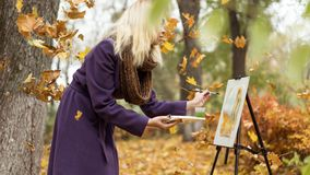 Blonde girl artist draws among falling leaves in the autumn park. Young beautiful girl artist with blonde hair in purple coat drawing a picture on the easle royalty free stock images