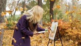 Blonde girl artist draws among falling leaves in the autumn park. Young beautiful girl artist with blonde hair in purple coat drawing a picture on the easle royalty free stock photos