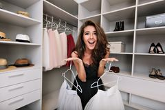 Young beautiful girl asks for help in choosing clothes in a dressing room. She smiles and looks in camera. She`s dressed. In black dress . Expressing true stock image