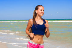 Young beautiful girl athlete  on the beach Stock Photo