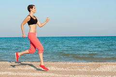 Young beautiful girl athlete playing sports on the beach Stock Photo