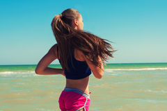 Young beautiful girl athlete playing sports on the beach Stock Photos