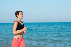 Young beautiful girl athlete runs with a player on the beach Stock Photos
