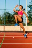 Young, beautiful girl athlete in sportswear doing warm-up at the stadium Royalty Free Stock Photo