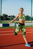 Young, beautiful girl athlete in sportswear doing warm-up at the stadium Royalty Free Stock Images