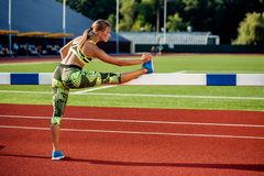 Young, beautiful girl athlete in sportswear doing warm-up at the stadium Royalty Free Stock Photos