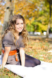 The young beautiful girl in autumn wood. Sits on a white plaid Royalty Free Stock Image