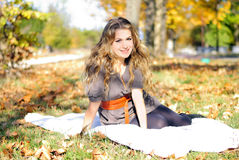 The young beautiful girl in autumn wood. Sits on a white plaid Stock Photos