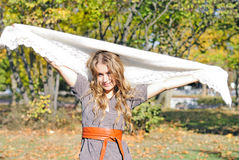 The young beautiful girl in autumn wood. With a white woolen scarf Royalty Free Stock Images