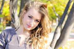 The young beautiful girl in autumn wood. On the sun Stock Photo