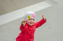 Young beautiful girl baby in a red jacket and white hat playing on the playground in the skate park, inhaling the aroma of yellow Royalty Free Stock Photos