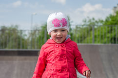 Young beautiful girl baby in a red jacket and white hat playing on the playground in the skate park, smiling and having fun Stock Photo