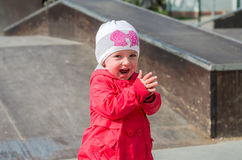 Young beautiful girl baby in a red jacket and white hat playing on the playground in the skate park, smiling and having fun Stock Image