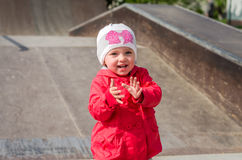 Young beautiful girl baby in a red jacket and white hat playing on the playground in the skate park, smiling and having fun Royalty Free Stock Image