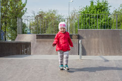 Young beautiful girl baby in a red jacket and white hat playing on the playground in the skate park, smiling and having fun Royalty Free Stock Photo
