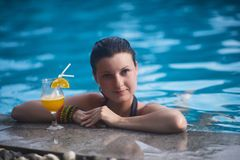Young beautiful girl on the background of a beautiful blue water, next to which is orange juice royalty free stock photos