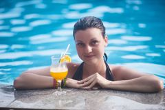 Young beautiful girl on the background of the pool, next to which is orange juice stock photography