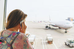 Young beautiful girl with a backpack next to the panoramic windows of the passenger terminal international airport Royalty Free Stock Photography
