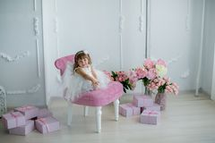 Young beautiful girl ballerina in a white pink dress is standing in a white room near a white table is holding a bouquet stock photos
