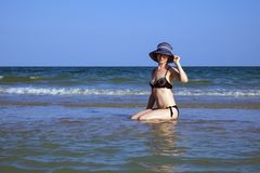 Young beautiful girl in a bathing suit and a striped hat is sitting on the seashore with her hand on the brim hat. Young beautiful girl in a bathing suit and a royalty free stock image