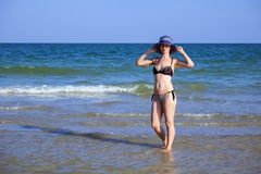 Young beautiful girl in a bathing suit and a striped hat is standing in the sea with her hands on the brim hat. Young beautiful girl in a bathing suit and a royalty free stock photo