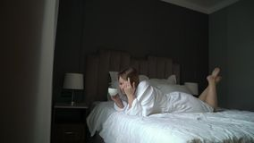 Young beautiful girl in bathrobe drinking coffee at the morning stock footage