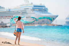 Young beautiful girl on the beach background big cruise ship. Stock Image