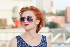 Young beautiful girl with beautiful appearance. Red-haired woman with a pretty face at sunset. A charming, smiling woman portrait Stock Image