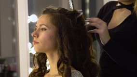 Young beautiful girl in beauty salon. Hairdresser-stylist makes the girl`s hair. The hairdresser curls the hair with a. Styler and stacks them. 4K. Close-up stock footage