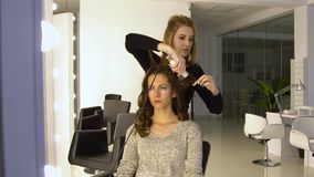 Young beautiful girl in beauty salon. Hairdresser-stylist makes the girl`s hair. The hairdresser curls the hair with a. Styler and stacks them. 4K. The middle stock footage
