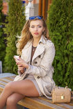 Young beautiful girl in a beige coat, calling by phone, sitting Royalty Free Stock Image