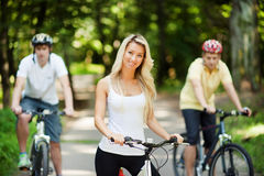 Young beautiful girl on a bicycle with two men in the background. Outdoors Royalty Free Stock Images