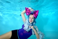 Young beautiful girl with a big bow on her head is swimming and posing underwater in the pool. Portrait. Horizontal view. The view. From the bottom Royalty Free Stock Images