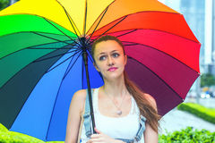 Young beautiful girl with a big colorful umbrella on the background of the city. The girl dreamily looking up. Stock Image