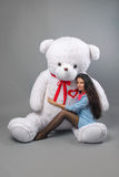 Young beautiful girl with big teddy bear soft toy happy smiling and playing on grey background Stock Photos