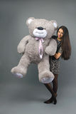 Young beautiful girl with big teddy bear soft toy happy smiling and playing on grey background Royalty Free Stock Photography