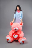 Young beautiful girl with big teddy bear soft toy happy smiling and playing on grey background.  stock images