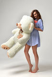 Young beautiful girl with big teddy bear soft toy happy smiling Stock Photo