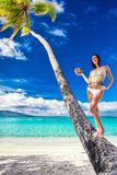 Young beautiful girl in bikini with coconut on the palm tree on. A tropical beach Royalty Free Stock Photos