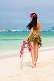Young beautiful girl in a bikini of flowers on the tropical beach. stock photo