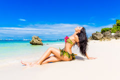 Young beautiful girl in a bikini of flowers on the tropical beach. stock photos