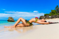 Young beautiful girl in a bikini of flowers on the tropical beach. stock images