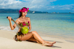 Young beautiful girl in a bikini made of flowers sitting on a tropical beach and coconut with a machete. Blue sea in the backgroun Stock Images