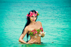 Young beautiful girl in a bikini made of flowers in the tropical Stock Photo