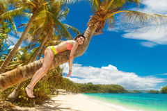 Young beautiful girl in bikini on the palm tree on a tropical be Stock Photos