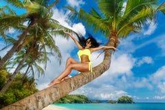 Young beautiful girl in bikini on the palm tree on a tropical be Stock Photo