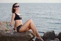 Young beautiful girl in bikini sits on stone near sea with bottle of water Royalty Free Stock Image